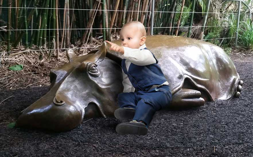 Toddler playing on hippo sculpture in play area at San Diego Zoo.