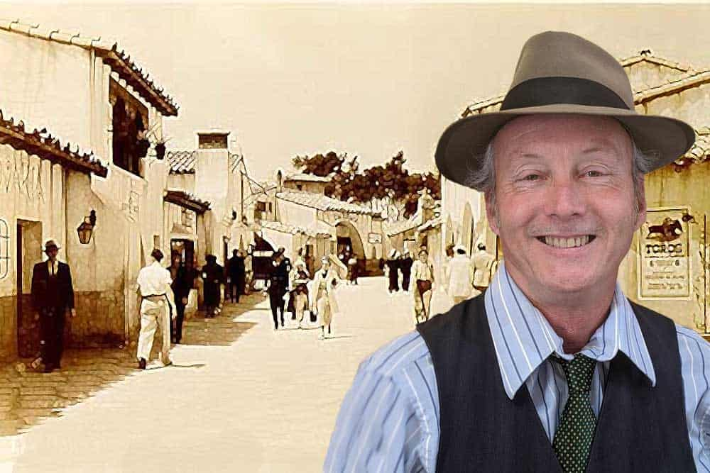 Spanish Village's historian and tour guide Jeffrey Iles in front of an 1940's photo of the Village.