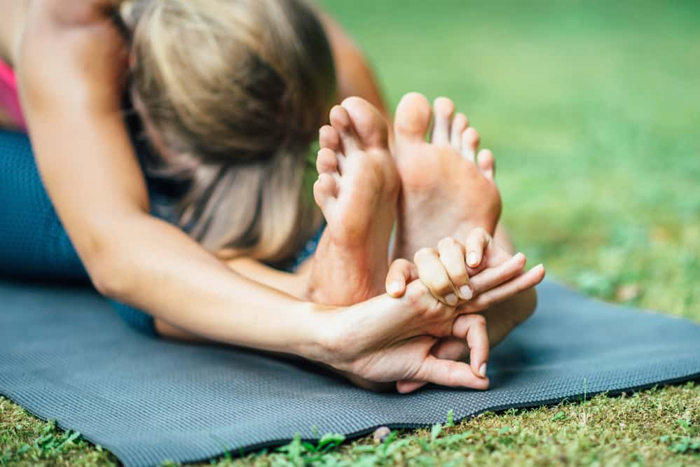 Woman doing Yoga, seated forward bend outside on a mat.