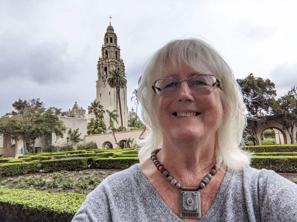 Nancy Ulrich, founder of SanDiegoing.com in Balboa Park's Alcazar Garden with the California Tower in the background.