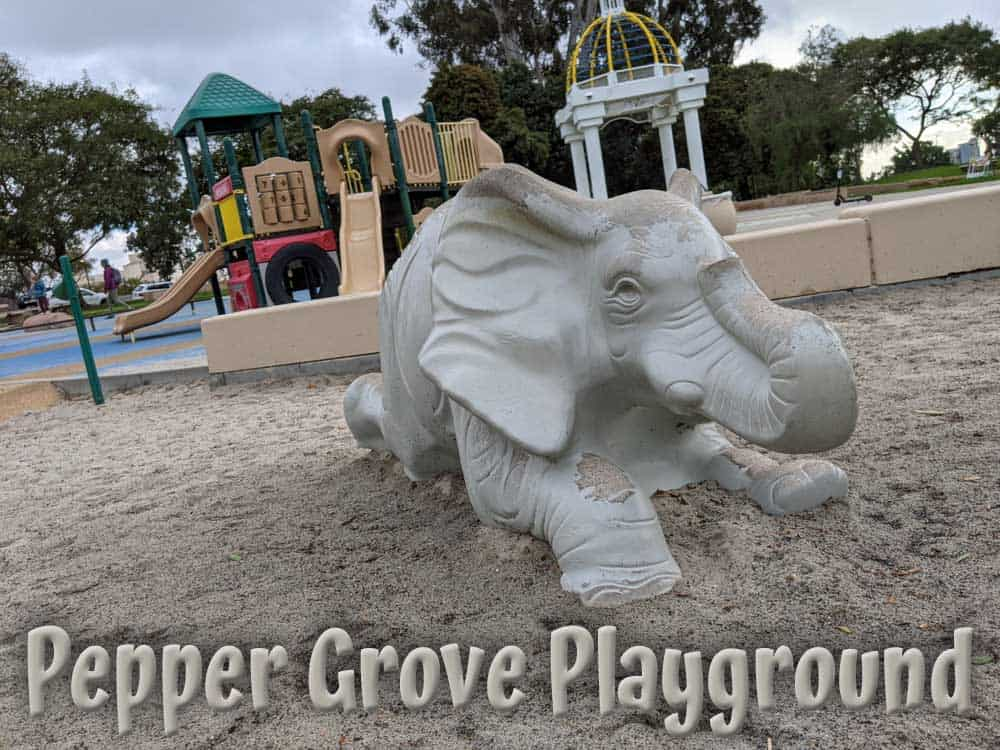 Balboa Park - Pepper Grove Playground elephant sculpture in sandbox with climbing and sliding structures in the background.